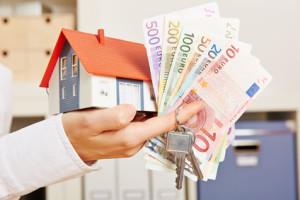 Hand mit Haus und Geld und Schlüssel